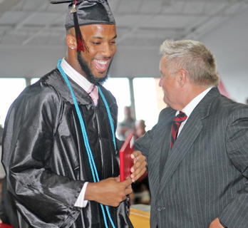 TCHS graduate Brandon Berry cracks a smile after receiving his diploma from superintendent Roger Cook