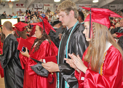 From right to left, Bryn Alston, Spencer Armstrong (foreground) and other Taylor County seniors clap after the benediction, given by classmate Grant Cox