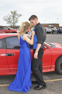 Dressed in royal blue, LeAnn LaJudice pins a boutonniere on Benjamin Fisher's matching vest before the TCHS prom.