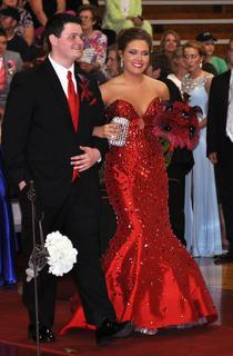 In a striking red mermaid style dress, Grace Bertram walks down the TCHS prom runway with Matthew Hall.