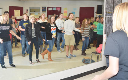"Show choir members watch themselves in a mirror as they sing songs from ""Aladdin."""