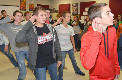"Male show choir members sing and perform choreography during a medley of songs from ""Aladdin."""