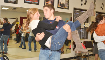 """Show choir member Grant Cox lifts Kassie Miller during a medley of songs from """"Aladdin."""""""