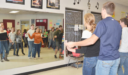 Show choir members, dancing in couples, watch themselves in a mirror as they perform.