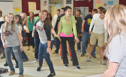"""The female members of the show choir watch themselves in a mirror as they sing and dance to an """"Aladdin"""" medley."""