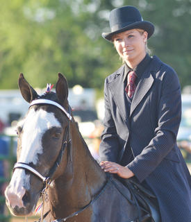 Kim Dalcerzak of Monticello smiles as she in this year's Tommie Johns Memorial Championship Horse show at the fair on Saturday.