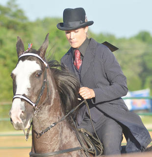 Kim Dalcerzak of Monticello rides her horse in this year's Tommie Johns Memorial Championship Horse show at the fair on Saturday.