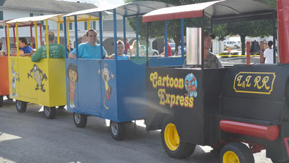 Children ride on a train to the Family Fun Zone.