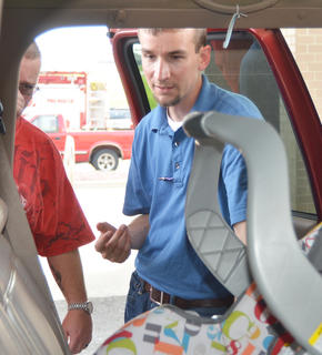 DeShaun Bailey, program coordinator for the Kentucky Office of Highway Safety's child passenger safety program, tells Campbellsville resident Jordan Vineyard how a car seat should be installed.
