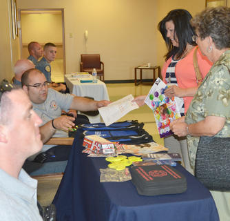 Campbellsville Fire & Rescue firefighter Brent Lile passes out fire safety information to parents. At left is firefighter Aaron Fields.