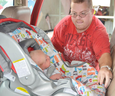 Tim Vineyard of Campbellsville places his son, Jordan, 10 days old, in his car seat for state officials to see if it's properly installed.