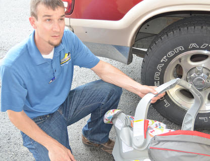 DeShaun Bailey, program coordinator for the Kentucky Office of Highway Safety's child passenger safety program, explains how a car seat should be installed.