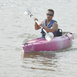 Drew Skaggs of Campbellsville paddles his way to shore to complete the kayak portion of the race.