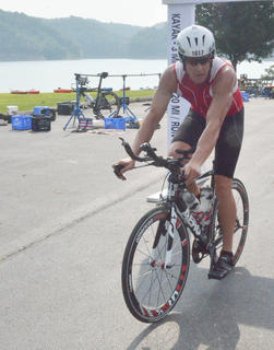 Nathan Rhodes of Campbellsville finishes the biking portion of the triathlon. He is in training for an IRONMAN race later this month in August. Rhodes, who works for Kentucky State Police, accidentally shot himself in the foot about a year ago.