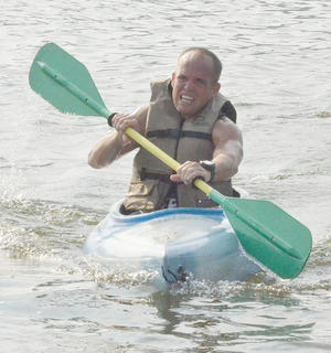 Weldon Riggs paddles his way to shore in the kayak portion of the race.