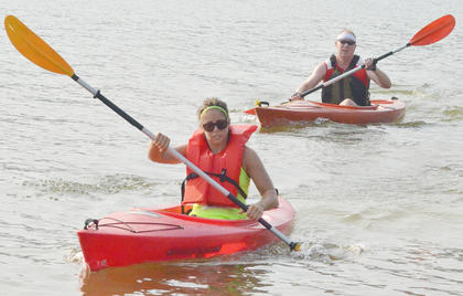 Katie White of Campbellsville, in front, and Craig Devine of Lebanon paddle to shore in the kayak portion of the race.