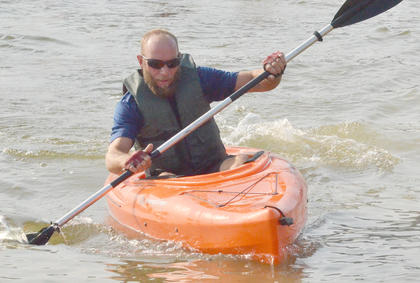Brandon Scott paddles to shore in his kayak.
