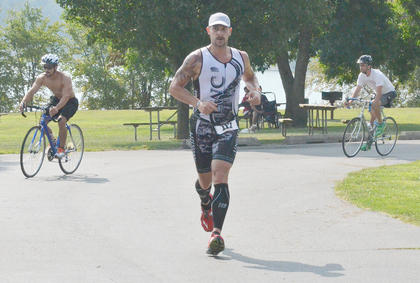 Chris Schmidt finishes the 5K run portion of the race as other participants complete the 20-mile bike ride.