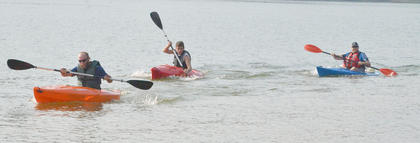 Kayakers make their way to shore as they complete the first portion of the race.
