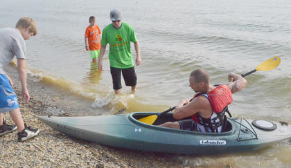 Chris Schmidt of Columbia comes ashore as he completes the kayak portion of the race.