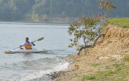 Scott Brewster paddles to shore in his kayak.