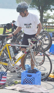 Scott Brewster puts his bike on a rack and prepares to run the last leg of the triathlon, a 5K.