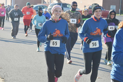 Ann Marie Pavy, at left, and Katie Irwin smile as they start the race.
