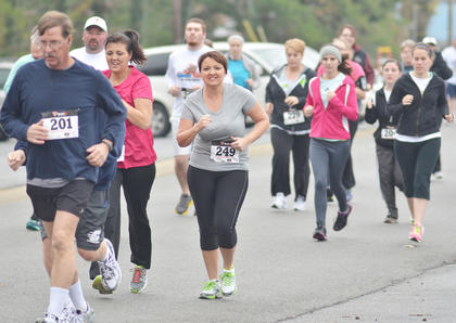 J. Robert Polley, at left, and Lisa Lyons lead a group of runners.