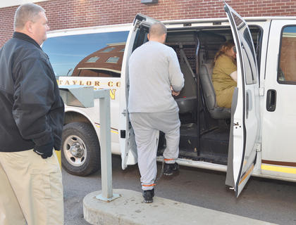 Sgt. Mark Pike watches as two inmates get inside a van he will drive so they can appear in court in another county.