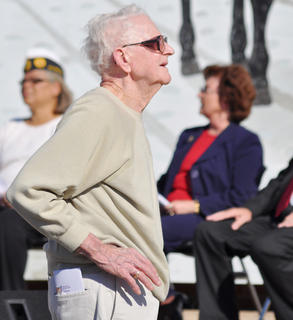 "Veteran Charlie Fox stands during ""God Bless the USA."""