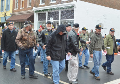 Vietnam veterans walk in the parade in their honor as confetti falls on them.