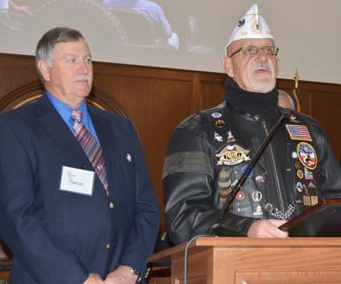 Vietnam veteran Bill Perkins, at left, listens as Phil Davis of the American Legion Post 83 accepts a proclamation proclaiming Dec. 14 as Welcome Home Vietnam Veterans Day, which will be hung at the legion.
