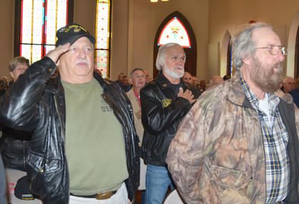 Veterans salute and place their hands over their hearts as they say the pledge to the flag.