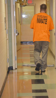 Inmate Matthew T. Nichols, who spends his days cleaning at the jail, walks down the hallway. Inmates spend their time doing many jobs at the jail, from laundry to serving lunch to cleaning.