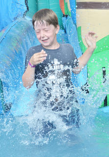 Conner Collette, 7, of Campbellsville, closes his eyes as he slides down this inflatable water slide into a pool of water at the Family Fun Zone.