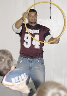 """<div class=""""source"""">Calen McKinney</div><div class=""""image-desc"""">CU football player Anthony Lewis holds a target for Matthew Haywood, 9, to throw a football through.</div><div class=""""buy-pic""""><a href=""""/photo_select/20817"""">Buy this photo</a></div>"""