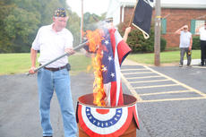 "<div class=""source"">Jeff Moreland</div><div class=""image-desc"">Jim Bright of Edwards-O'Banion American Legion Post 82 holds an American flag over a barrel during a retirement ceremony for this and other worn and tattered flags Saturday morning.</div><div class=""buy-pic""><a href=""/photo_select/66177"">Buy this photo</a></div>"