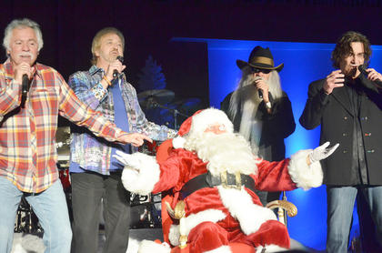 """The Oak Ridge Boys sing """"Here Comes Santa Claus"""" after Santa paid a visit to the boys and girls in the audience. From left are Joe Bonsall, Duane Allen, William Lee Golden and Richard Sterban."""