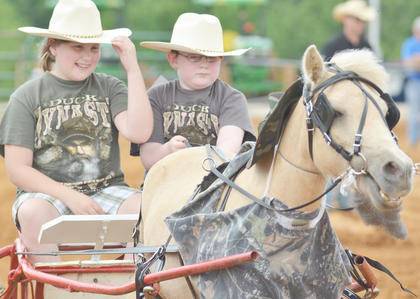 Grace Malone of Campbellsville holds on to her hat as her brother, Cade, pulls the reigns on their horse.