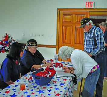 American Legion members Gina Cox and Laurie Mandi wait to hand out poppies as Henrietta Anderson signs the American Legion veteran's luncheon guest list for herself and her husband, Ted, an Army veteran.