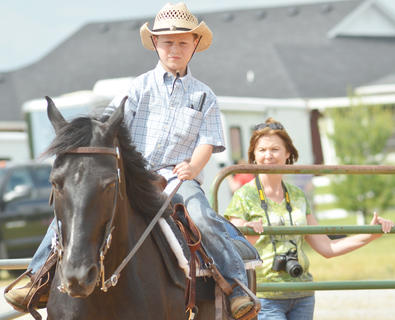 Chase Morris of Campbellsville rides his horse as his grandmother, Cary Noe, watches from a nearby gate.