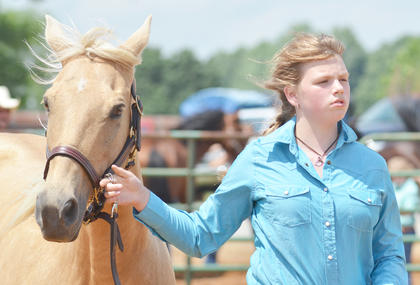 Gabriel Sharp of Campbellsville holds her horse as she is judged.
