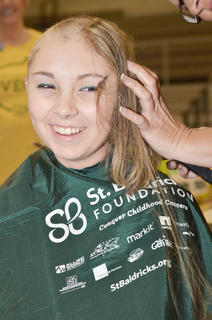 Tonya Ferrie shaves her daughter Ariel's head. Ariel battled cancer and has been in remission for nine years.