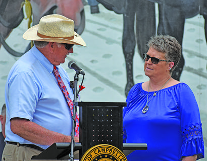Event organizer Bill Perkins honors Pattie Waters, who has performed at events honoring Taylor County veterans for more than 20 years. Her father was a veteran of the Korean War, her husband is a Vietnam veteran and her son is currently active in the military.