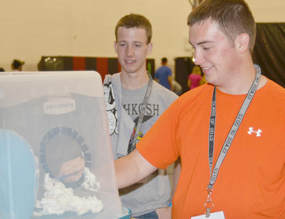 Marshall Bogues tries to shave a balloon without popping it while classmate Aaron Campbell watches.