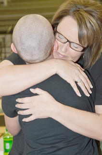 Tonya Ferrie hugs her daughter, Ariel, after shaving her head. Ariel battled cancer and has been in remission for nine years.
