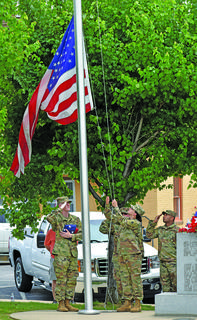 Private First Class Patrick Sullivan, of Jeffersontown (holding flag), Specialist Dillyn Graham (background), of Campbellsville, and Sergeant Joe Shabazz (right), of Campbellsville, salute the new flag as Private First Class Kelli Simpson, of Campbellsville, raises it back to half staff.