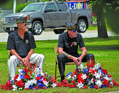 American Legion Post 82 Commander Phil Davis and Post 82 Vice Commander Gregg Parent watch the memorial service, waiting for their cue to place flowers on the Taylor County War Memorial.