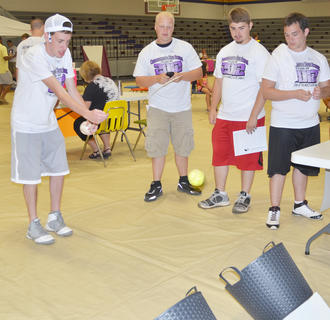 Chance Cox tries to throw a baseball in a basket while Mason Wethington, Kevin Caswell and Coty Hadyen watch.