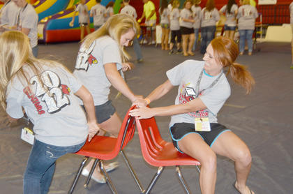 TCHS graduates laugh as they fight for chairs during a musical chairs game.